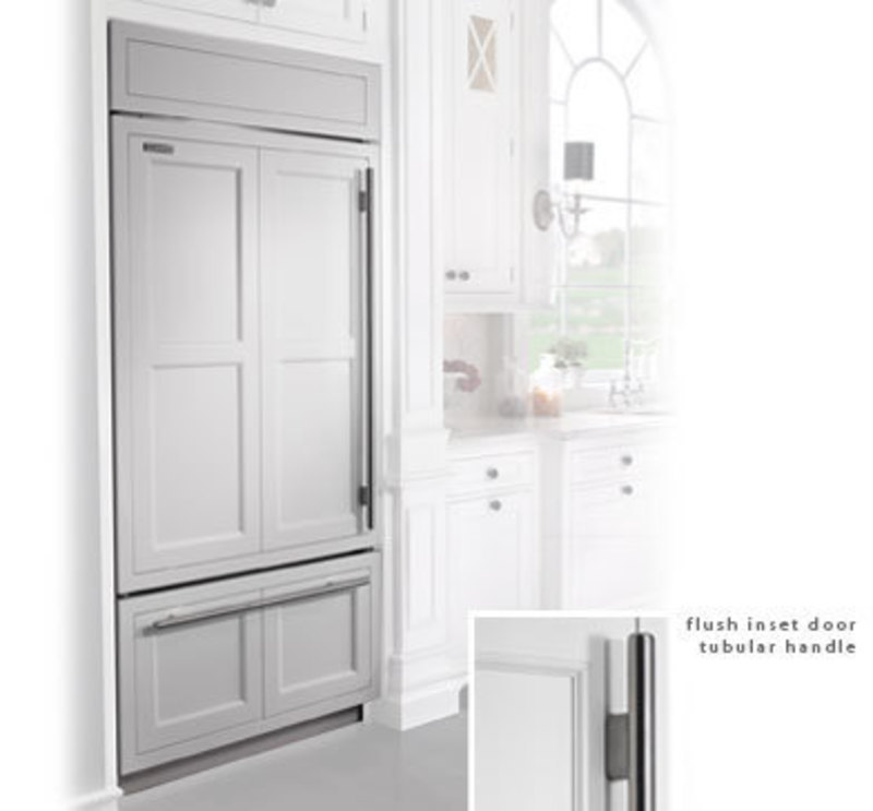 Built in refrigerator with a framed cabinet style overlay and applied handles