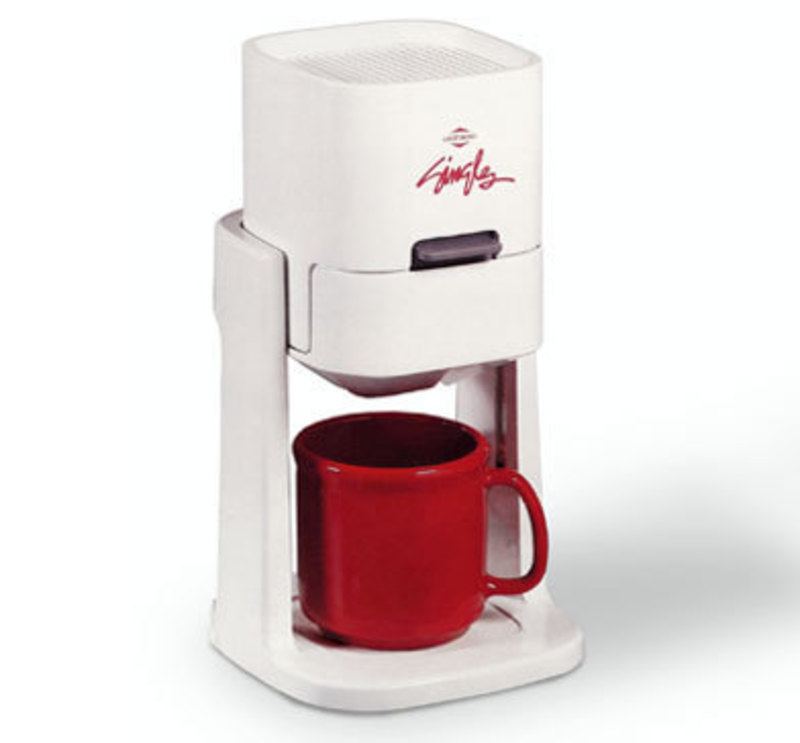 Three quarters front view of the singles coffee maker with a red coffee mug inside